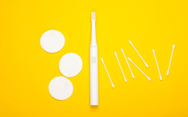 Flat lay composition of hygiene products. toothbrush, cotton pads, ear sticks on yellow background. top view