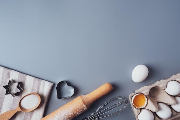 フラットレイ構成、灰色の背景にクッキーを焼くための材料、コピースペース。バレンタインデー、母の日、父の日のためにクッキーやカップケーキを作る。お祝い料理のコンセプト。