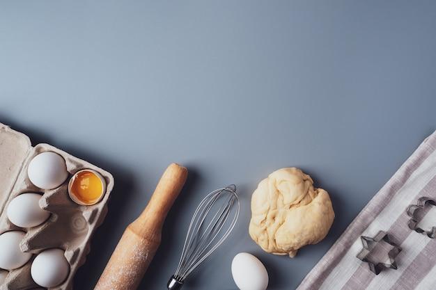 플랫 레이 구성, 회색 배경에 쿠키를 굽기 위한 재료, 복사 공간. 발렌타인 데이, 어머니의 날, 아버지의 날을 위한 쿠키 또는 컵케이크 만들기. 축제 음식의 개념입니다.