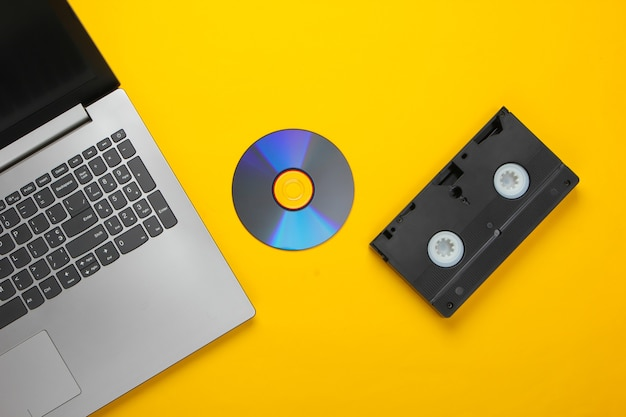 Flat lay composition of laptop, cd disc, audio cassette on a yellow