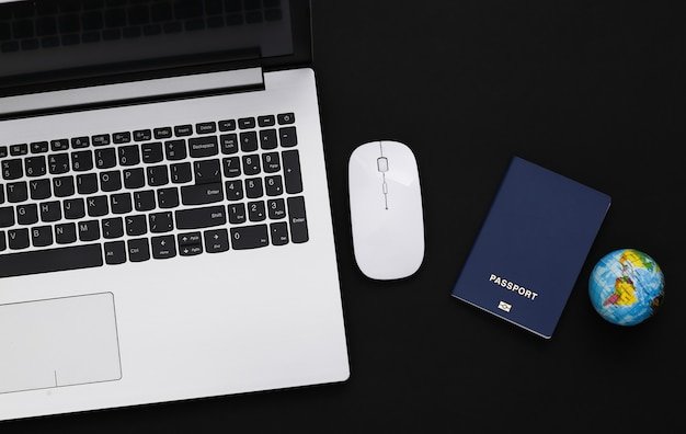 Flat lay composition of laptop and travel accessories on black background. tourism. top view.