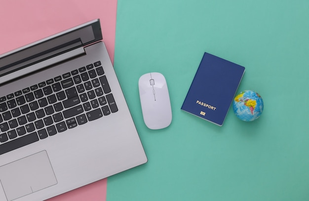 Flat lay composition of laptop and travel accessories on pink blue pastel background. tourism. top view.