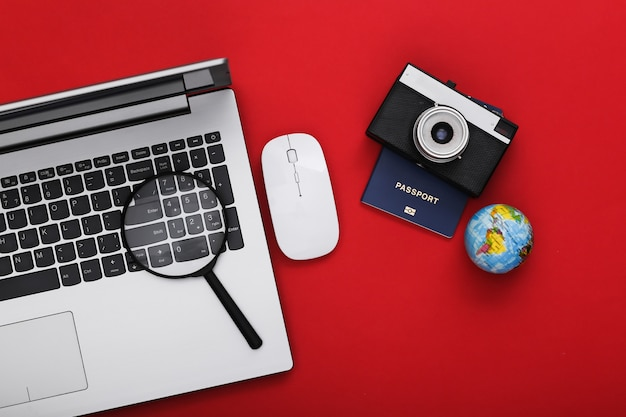 Flat lay composition of laptop and travel accessories on red background. tourism. top view.