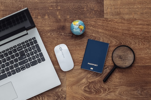 Flat lay composition of laptop and travel accessories on a wooden floor. tourism. top view.