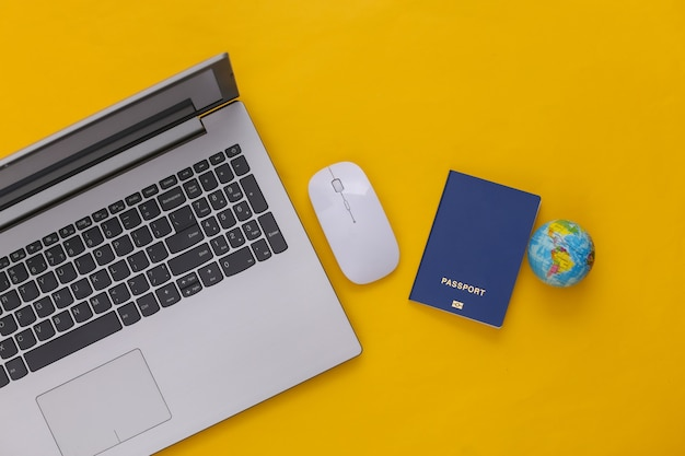 Flat lay composition of laptop and travel accessories on yellow background. tourism. top view.