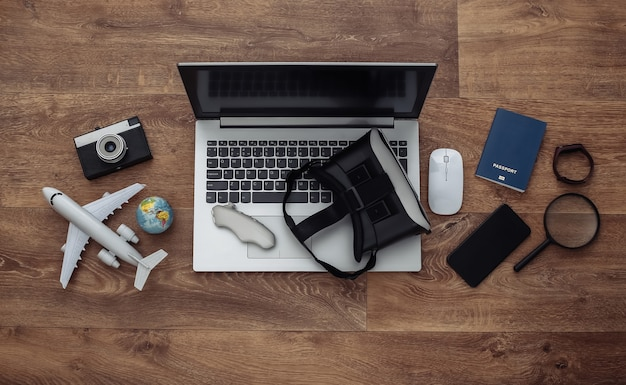 Flat lay composition of laptop and vr headset, travel accessories on a wooden floor. virtual tourism. top view.
