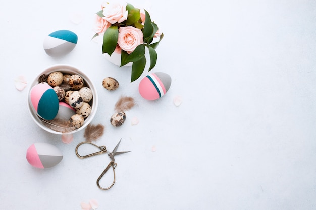 Flat lay composition of naturally-dyed quail egg and color easter eggs lying in tray on wihte tablewall with feather and pink roses. space for text