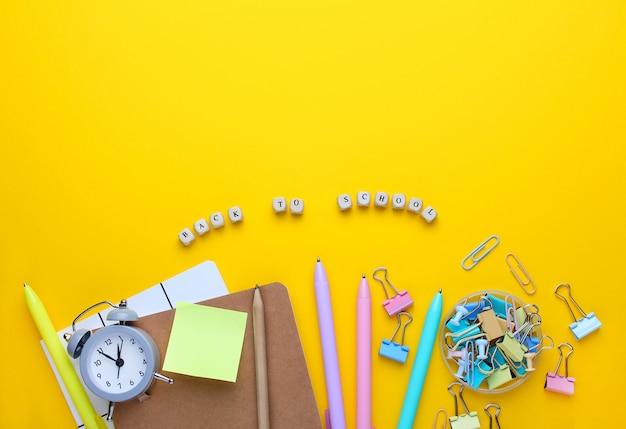 Flat lay composition of notebook, pencil, pens, binders, alarm clock.