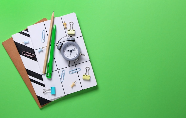 Flat lay composition of notebooks, pencil, pen, binders, alarm clock on green.