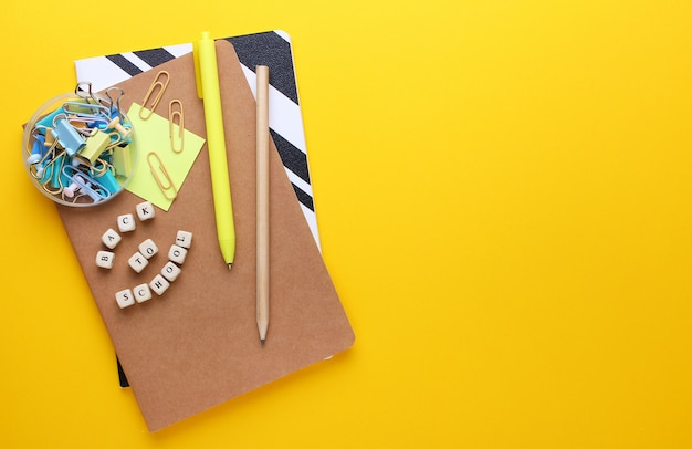 Flat lay composition of notebooks, pencil, pen, binders. copy space, yellow.