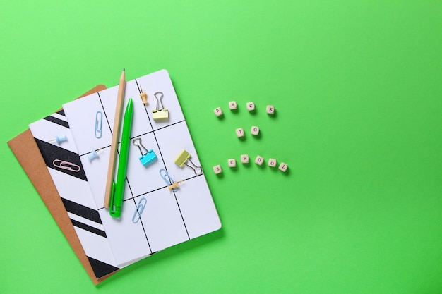 Flat lay composition of notebooks, pencil, pen, binders on green.