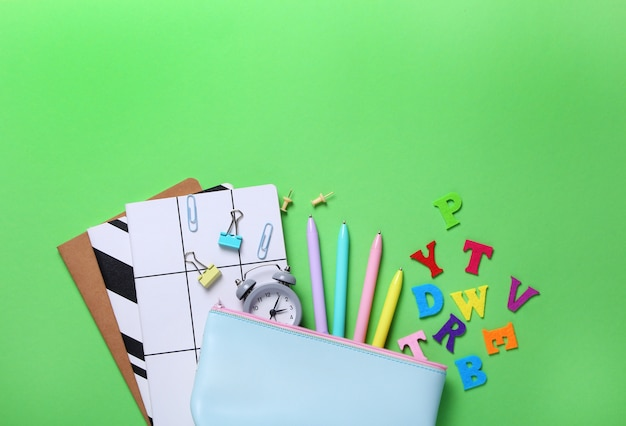 Flat lay composition of notebooks, pencil, pens, binders, alarm clock, color letters on green.