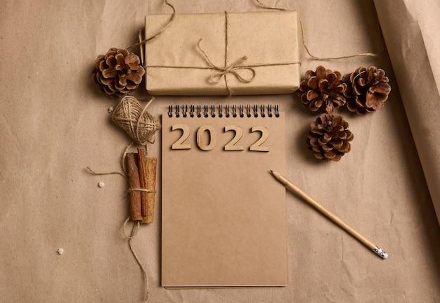 クラフト包装紙、松ぼっくり、シナモン、ロープ、メモ帳に鉛筆、段ボールの背景に空の空白の茶色の紙、コピー広告スペースのクリスマスプレゼントのフラットレイ構成
