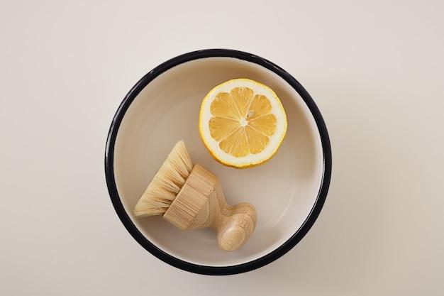 白い表面のプレートに、クリーニングブラシと黄色のハーフカットレモンのフラットレイ構成、上面図。無毒の家庭用洗剤のレシピの説明。環境にやさしい製品。