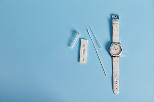 Плоский состав экспресс-теста на антиген covid-19 и ручные часы изолированы