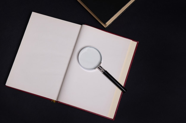 Плоская композиция из увеличительного стекла на открытой книге в твердой красной обложке, изолированной на черном фоне с пространством для текста. концепция дня учителя, знания, литература, чтение, эрудиция