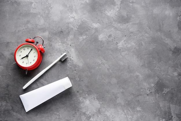 歯磨き粉のチューブと灰色の目覚まし時計付き歯ブラシのフラットレイアウト構成