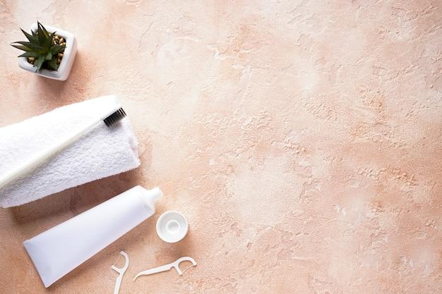 ベージュに白いタオルと歯磨き粉が入った歯ブラシのフラットレイアウト構成