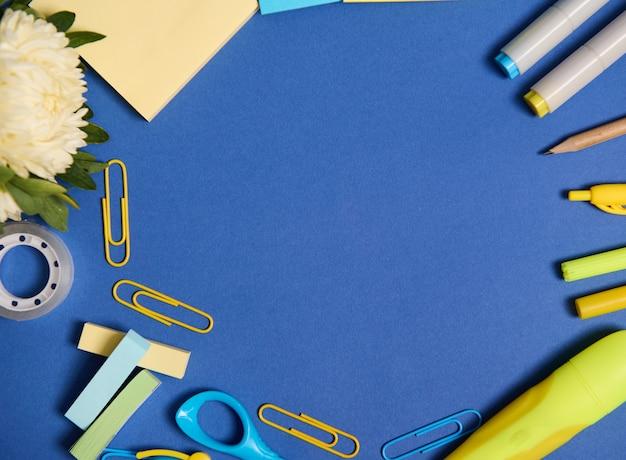 Плоская композиция из ассортимента школьных офисных принадлежностей в желтых тонах, изолированных на синем фоне, копией пространства. цветы астры и канцелярские принадлежности разбросаны по кругу. вид сверху.