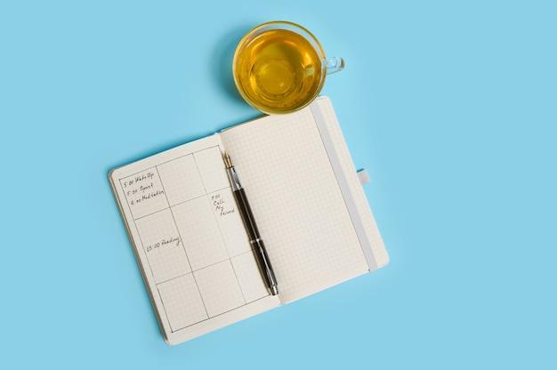 일정, 잉크 펜, 투명한 유리 컵의 차가 있는 열린 의제의 평평한 구성은 파란색 표면에 있습니다. 복사 공간이 있는 배경색입니다. 시간 관리, 마감일, 일정 개념
