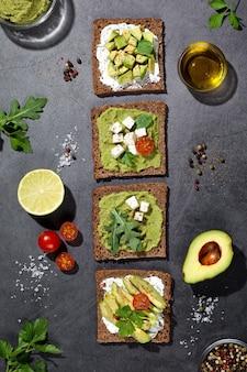 Плоская композиция из тостов с авокадо на темной основе. вертикальный формат.
