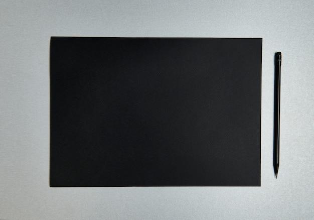 Плоская композиция из черного листа дизайнерской бумаги и черного деревянного карандаша на сером фоне. вид сверху