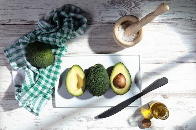 Плоская композиция из свежих авокадо на белой деревянной основе.