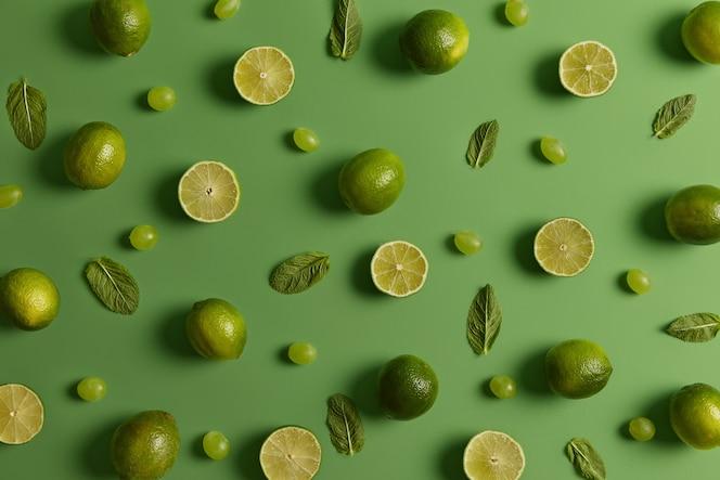 신선한 육즙 라임, 민트와 포도 녹색 배경 위에 절연 잎의 평면 위치 구성. 비타민이 가득한 열대 과일. 모히토 또는 레모네이드 재료. 감귤류와 음식 패턴
