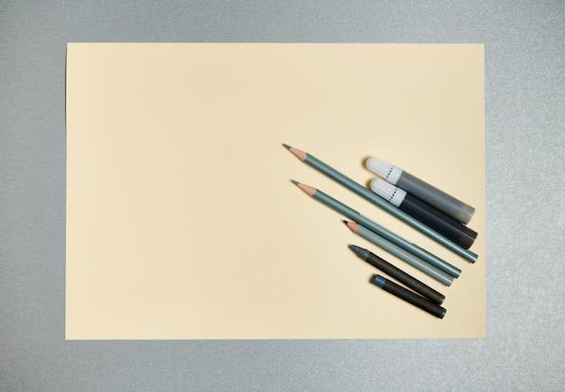 Плоская композиция из серых рисовальных инструментов на желтой акварельной бумаге. вид сверху на сером фоне