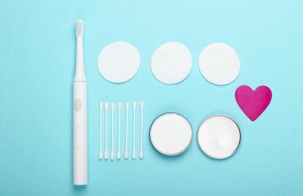 Плоская композиция средств гигиены. зубная щетка, ватные диски, ушные палочки, крем на синем фоне. вид сверху