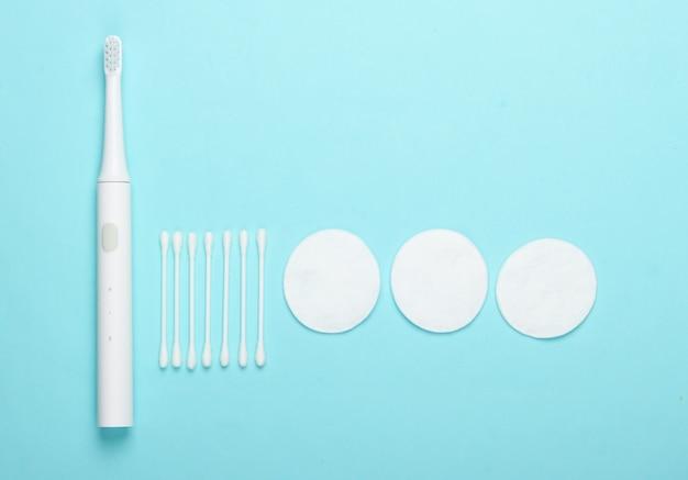 Плоская композиция средств гигиены. зубная щетка, ватные диски, ушные палочки на синем фоне. вид сверху