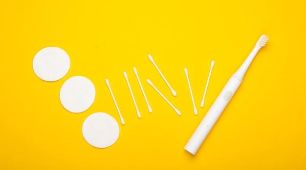 Плоская композиция средств гигиены. зубная щетка, ватные диски, ушные палочки на желтом фоне. вид сверху