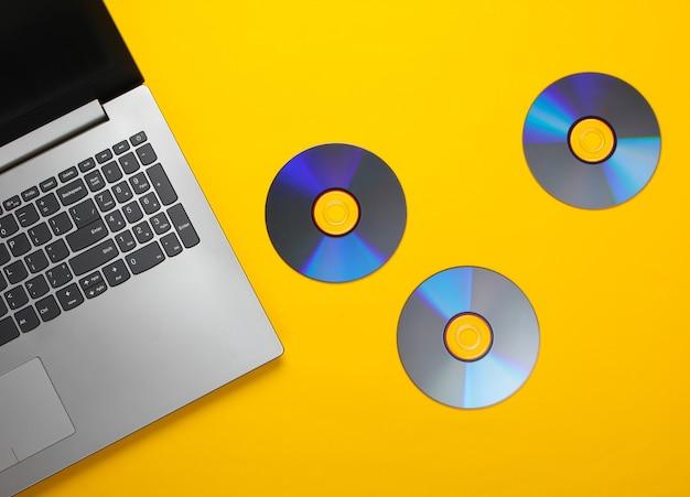 ラップトップのフラットレイ構成、黄色のcdディスク。