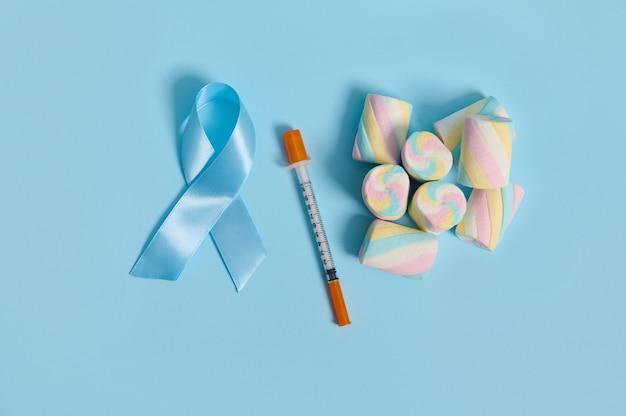 11月14日、世界糖尿病デーの医療広告用のコピースペースを備えたパステルカラーの背景に配置されたマシュマロ、青いサテンの認識リボン、インスリン注射器のフラットレイ構成