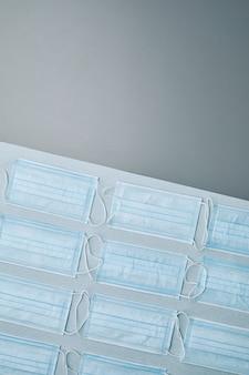 Плоская композиция медицинских масок, выложенных узором на сером фоне,