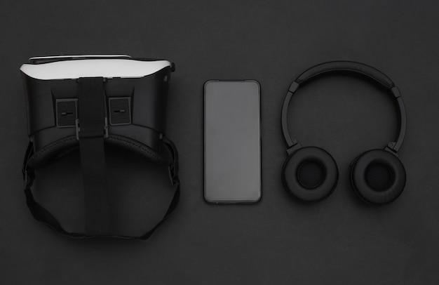 현대 가제트의 평평한 구성. 검은 배경에 vr 헬멧, 헤드폰 및 스마트폰. 평면도