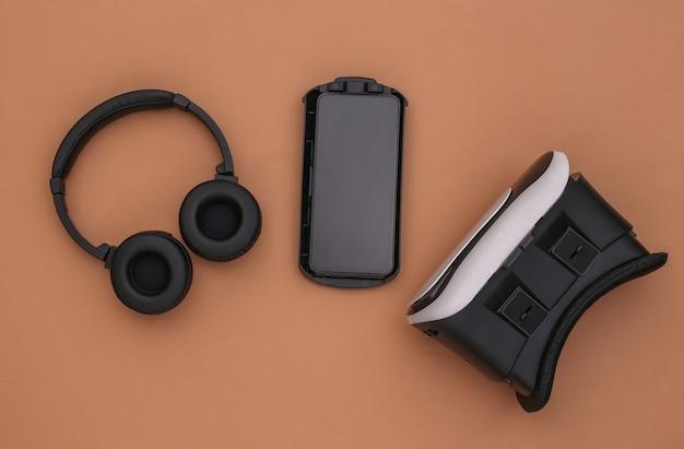 현대 가제트의 평평한 구성. 갈색 배경에 vr 헬멧, 헤드폰 및 스마트폰. 평면도