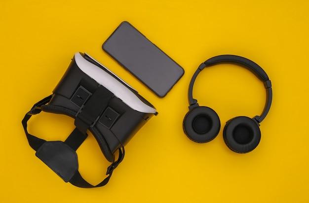 현대 가제트의 평평한 구성. 노란색 배경에 vr 헬멧, 헤드폰 및 스마트폰. 평면도