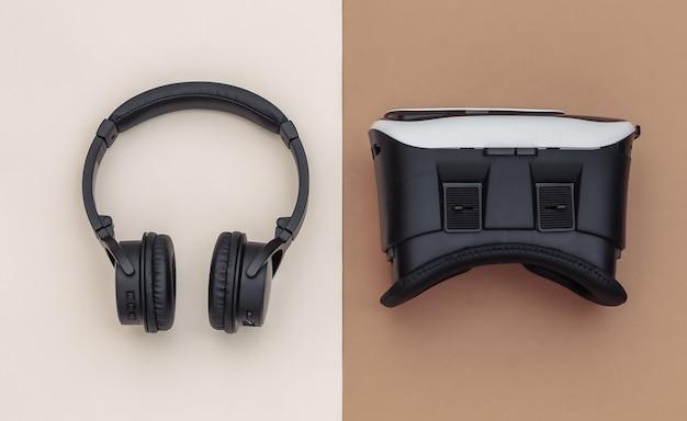 현대 가제트의 평평한 구성. vr 헬멧, 갈색 베이지색 배경에 헤드폰. 평면도