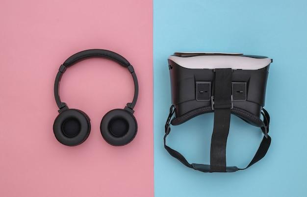 현대 가제트의 평평한 구성. vr 헬멧, 분홍색 파란색 배경에 헤드폰. 평면도