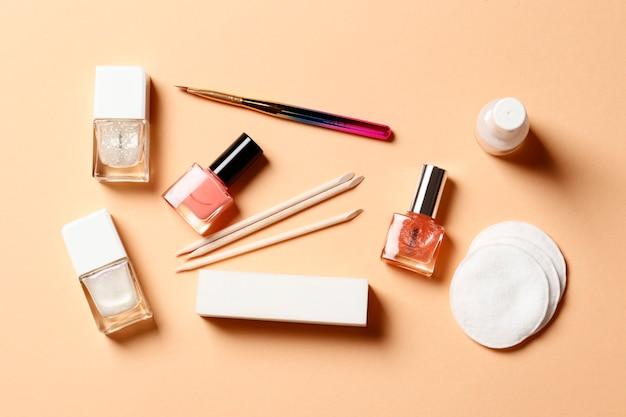 Плоская композиция из лаков для ногтей и маникюрных инструментов на розовом фоне