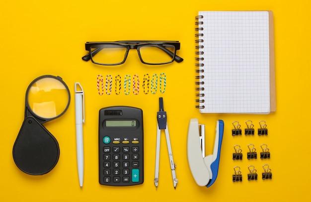 Плоская композиция из офисных инструментов, канцелярских товаров на желтом