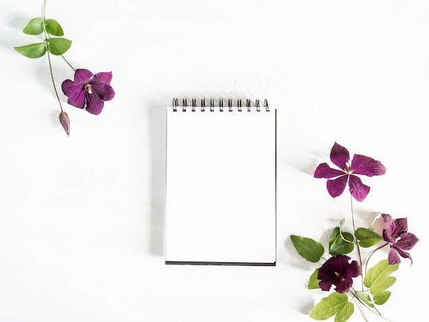 Плоские лежал композиция из фиолетового клематиса цветы и листья и блокнот с макетом чистого листа на белом фоне. вид сверху.