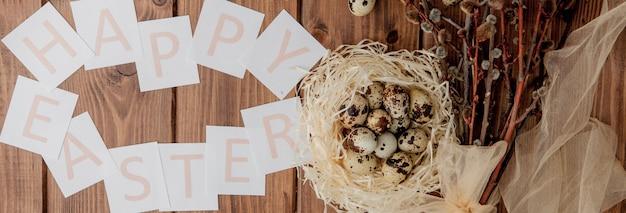 ウズラの卵と木製のテーブルにハッピーイースターのテキストとカードのフラットレイ構成
