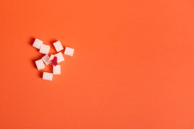 의료 광고를 위한 복사 공간이 있는 오렌지색 배경 위에 혈액 방울이 격리된 정제된 흰색 설탕 큐브의 평평한 구성. 세계 당뇨병의 날 인식 개념, 11월 14일