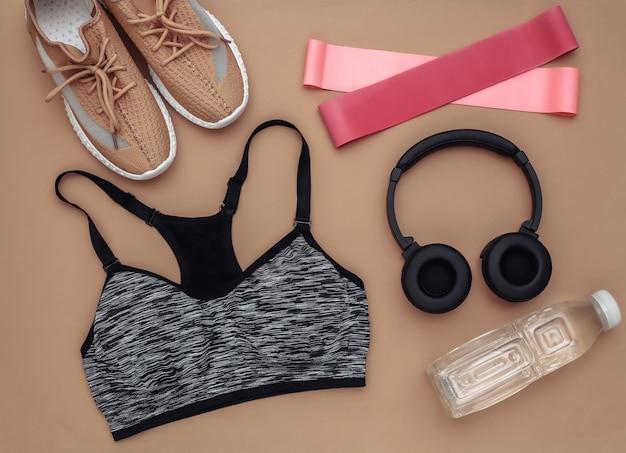 スポーツ用品、茶色の背景の服のフラットレイ構成。フィットネス、スポーツ、健康的なライフスタイルのコンセプト。上面図