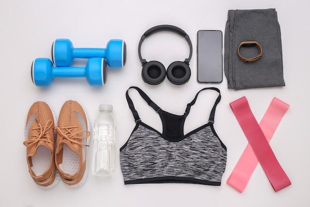 スポーツ用品、白い背景の服のフラットレイ構成。フィットネス、スポーツ、健康的なライフスタイルのコンセプト。上面図