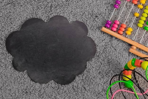 Плоская композиция из игрушек и шаблон сланца
