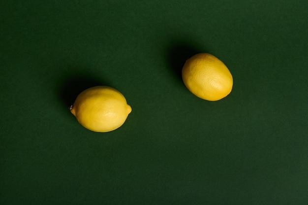 濃い緑色の背景に2つの明るい黄色のレモンのフラットレイ構成、柔らかな光でスタジオ撮影。食品の背景。ビーガンの健康的な食事。広告用のコピースペース