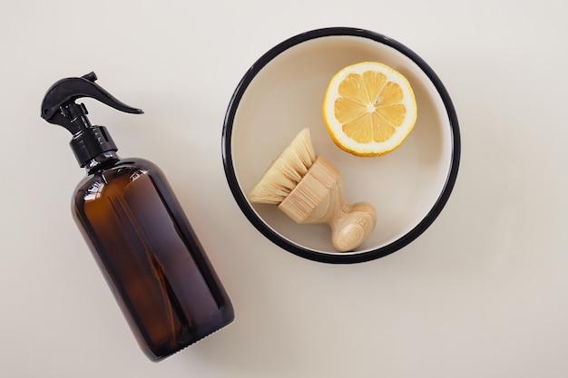 白い表面に調理器具と黄色のハーフカットレモンのフラットレイ組成物、上面図。無毒の家庭用洗剤のレシピのステップバイステップの説明。環境にやさしいクリーニングツールと製品。